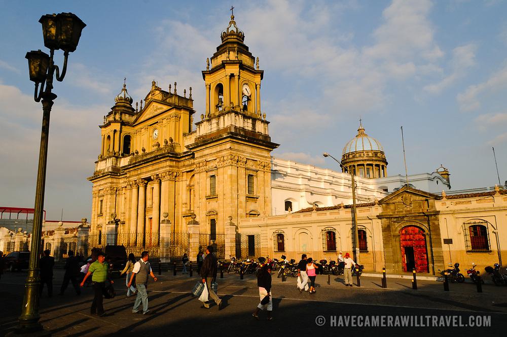 Locals walk in front of the Catedral Metropolitana facing Parque Central (officially the Plaza de la Constitucion) in the center of Guatemala City, Guatemala.