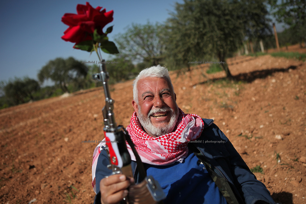 Abu Mohamed jokes with a rose sticked in his silver Kalashnikov. He has joint the armed resistance in Courine against Assad after beeing arrested by loyalists last year. (Attention: Only for PRINT. For all kinds of electronical publishing his face must be anonymized!!) Courine was been attacked by ground troops on February 22, 2012 (see archive images). aftermath air force helicopters shot  rockets several times into the 7000 inhabitants counting village south of Idlib city. Courine ist still a stronghold of opposition.
