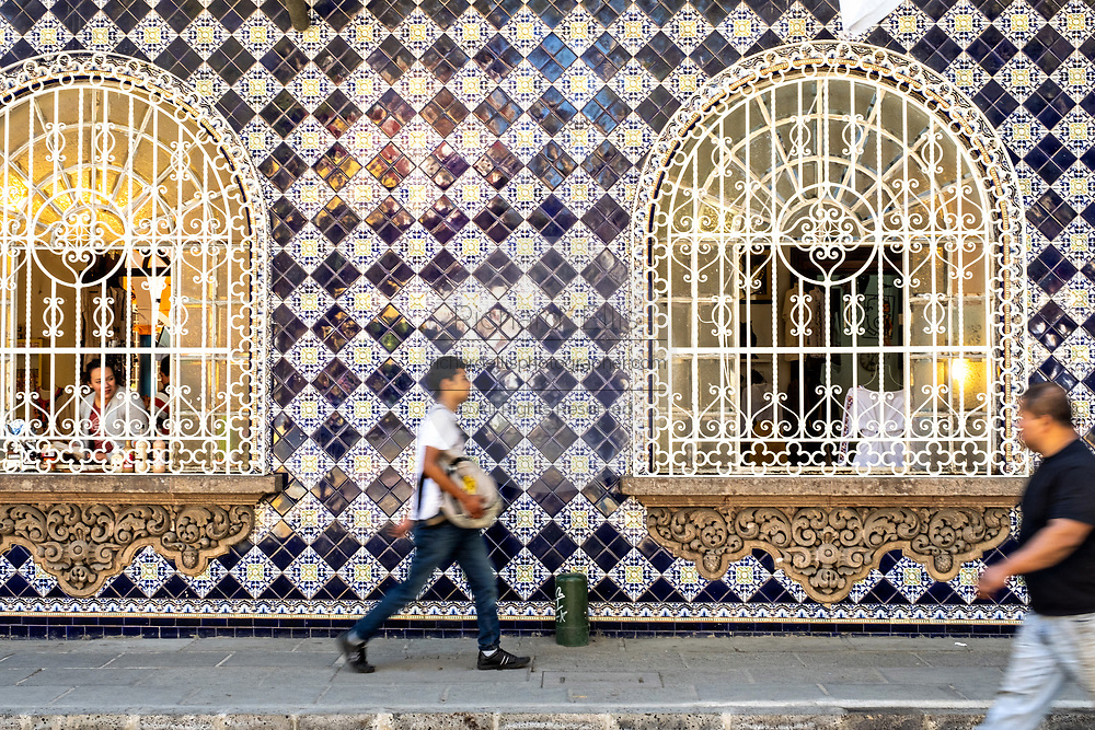 People walks past the colorful tiled Spanish colonial style building in the central historic district of Coatepec, Veracruz State, Mexico.