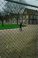 Nederland, Vught , 20030125. AMA Campus in Den Bosch. Jongen staat achter het hek op de campus. <br /> <br /> Het asielzoekerscentrum in de voormalige Isabella-kazerne in Vught is in september 2002 omgebouwd tot de eerste Nederlandse campus voor alleenstaande minderjarige asielzoekers (ama's). In het centrum moeten jongeren tussen 15 en 17 jaar worden voorbereid op een terugkeer naar hun moederland. <br /> Het is een  experiment, dat een jaar gaat duren. De ama-campus is het gevolg van het strengere beleid dat de vorige staatssecretaris van Justitie, Kalsbeek, voor de ama's in gang heeft gezet. Het Centraal Orgaan opvang Asielzoekers (COA) schotelt hen een strak dagprogramma voor, waarin onderwijs en recreatie de voornaamste elementen zijn. Het is de bedoeling dat zij het terrein niet verlaten, maar het is juridisch onmogelijk om de ama's dat te verbieden.