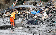 A worker uses a chainsaw to break up a tree in the mudslide near Oso, Washington as efforts continued to find victims March 26, 2014. The death toll from a massive landslide in Washington state stood at 24 on Wednesday, but the mud-stricken community braced for a higher body count as search teams combed through debris looking for scores of people still missing four days after the disaster. REUTERS/Rick Wilking(UNITED STATES)