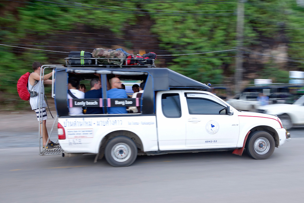 Tourists riding on the bumper of a crowded shared taxi, also known as a songthaew, on Koh Chang Island, Thailand.
