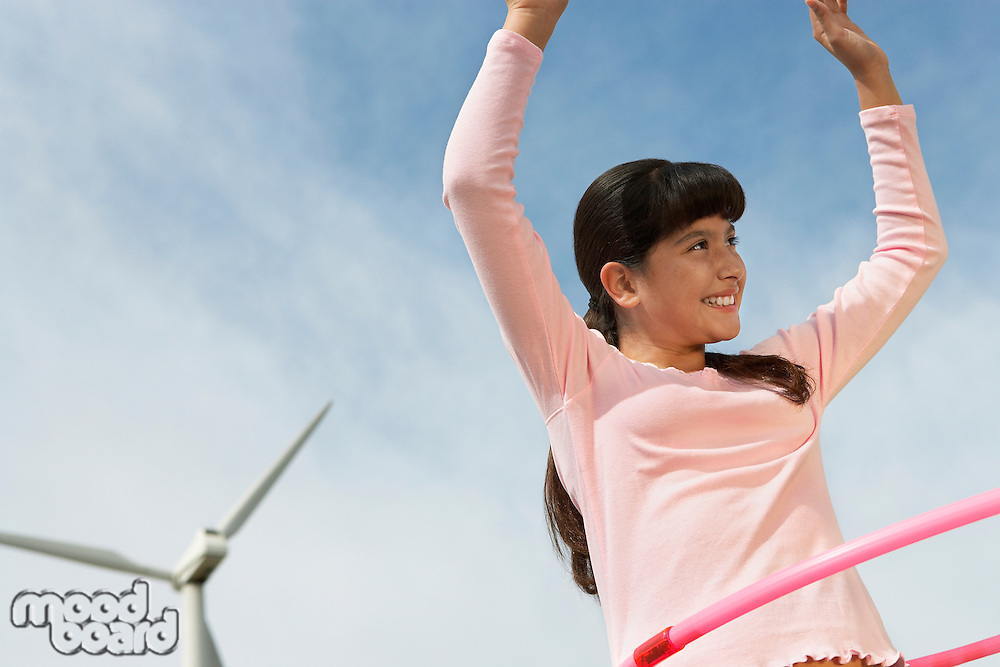 Girl (7-9) playing with hula hoop at wind farm
