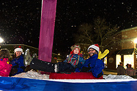 """Tubing"" down Main Street with a little extra snowfall on Gunstock Mountain's float Sunday evening during the Holiday Parade with ""Light Up Laconia"".  (Karen Bobotas/for the Laconia Daily Sun)"