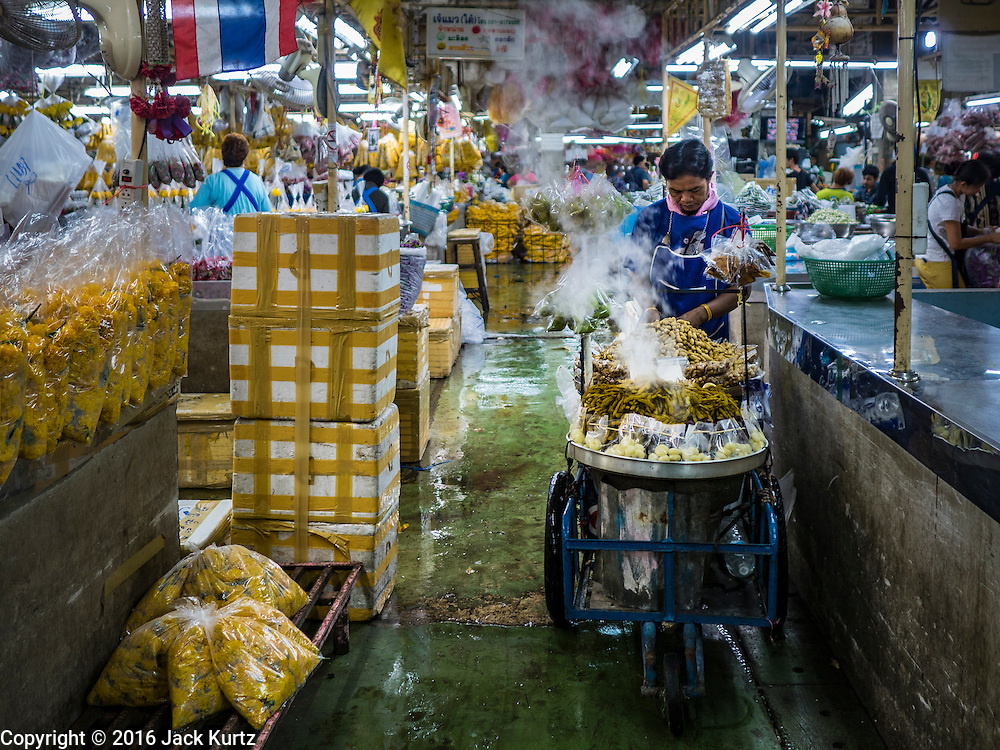 24 FEBRUARY 2016 - BANGKOK, THAILAND: A snack vendor pushes his steaming cart of peanuts through Pak Khlong Talat in Bangkok. Bangkok government officials announced this week that vendors in Pak Khlong Talat, Bangkok's well known flower market, don't have to move out on February 28. City officials are trying to clear Bangkok's congested sidewalks and they've cracked down on sidewalk vendors. Several popular sidewalk markets have been closed in recent months and the sidewalk vendors at the flower market had been told they would be evicted at the end of the month but after meeting with vendors and other stake holders city officials relented and said vendors could remain but under stricter guidelines regarding sales hours. The flower market is one of the best known markets in Bangkok and has become a popular tourist destination.        PHOTO BY JACK KURTZ