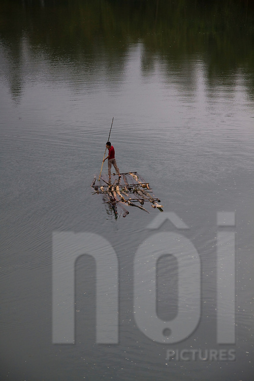 Man crossing a river on a rudimentary raft in Cao Bang area, Vietnam, Asia