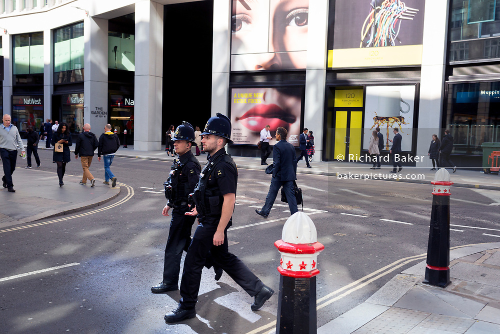 A pair of eyes and City police officers on Fenchurch Street - in the heart of the capital's financial district (aka The Square Mile),  on 25th September 2018, in London, England.