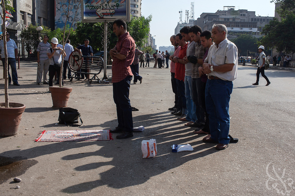 "Supporters of deposed Egyptian President Mohamed Morsi pray along Ramsis street during the August 16, 2014 ""Day of Rage"" protests around Ramsis square in Cairo, Egypt."