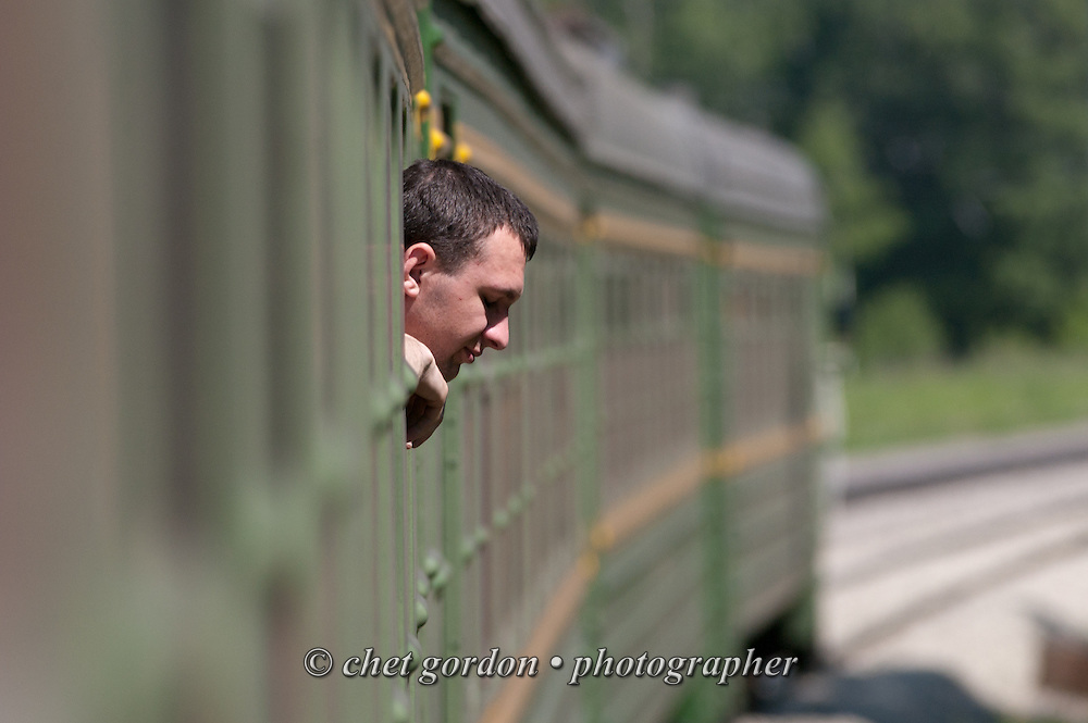 "A passenger peers from his window onboard an ""electricka"" or commuter train en route to Tiaga, Siberia Russian Federation on Monday, June, 13, 2005."