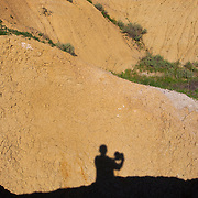 Photographer's selfie in the Badlands National Park in southwestern South Dakota protects 242,756 acres of sharply eroded buttes, pinnacles, and spires. The park protects an expanse of mixed-grass prairie where bison, bighorn sheep, ( Ovis canadensis ) and prairie dogs live today.  Photography by Jose More