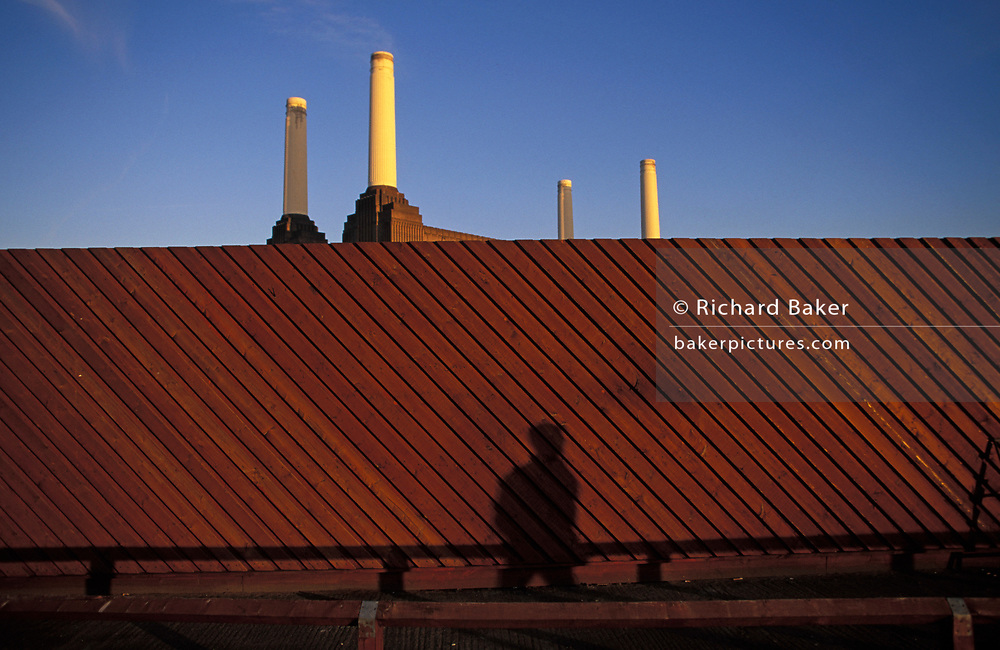 The shadow of a person appears on a hoarding that surrounds the four chimneys of Battersea Power Station before its massive redevelopment in the 2010s, on 25th March 1998, in London, England.