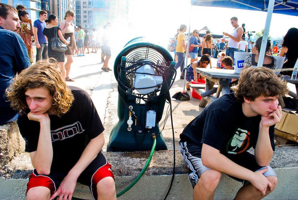 Two underage pool partiers sit in boredom behind a mist spraying fan at the JELLY Pool Party free concert series East River State Park, Williamsburg, Brooklyn, New York