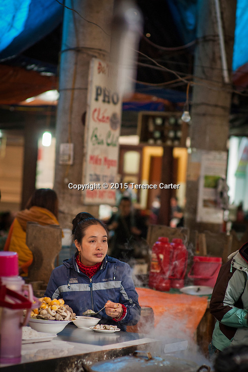 A woman takes lunch in the markets of Sapa, Vietnam.