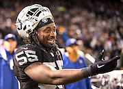 Oakland Raiders outside linebacker Sio Moore (55) laughs as he points from the sideline as a seagull parades around the field during the NFL week 12 regular season football game against the Kansas City Chiefs on Thursday, Nov. 20, 2014 in Oakland, Calif. The Raiders won their first game of the season 24-20. ©Paul Anthony Spinelli