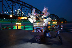 A Chinese street vendor sells cotton candy beside the Sino-Korean Friendship Bridge (extreme L) connecting Sinuiju, North Korea, and the Yalu River Bridge (L) along the Yalu River in the Chinese city of Dandong, Liaoning Province, China on 05 April 2013. North Korea recently moved a ballistic missile to its east coast in a seeming show of strength or in readiness for a launch, Yonhap News Agency reported 04 April. Tensions have risen as Pyongyang's third nuclear test in February led to a tightening of international sanctions against it, with its closest ally China calling for calm on all sides.