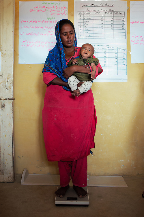 Mother Najma Muhammad weighs her child in the government health clinic in the village of Sheer Ali Shah, Thatta, Sindh, Pakistan on July 1, 2011. Baby Dilbar Malooka, 7 months old suffers from severe malnutrition.