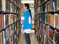 Young woman standing by bookshelf in library