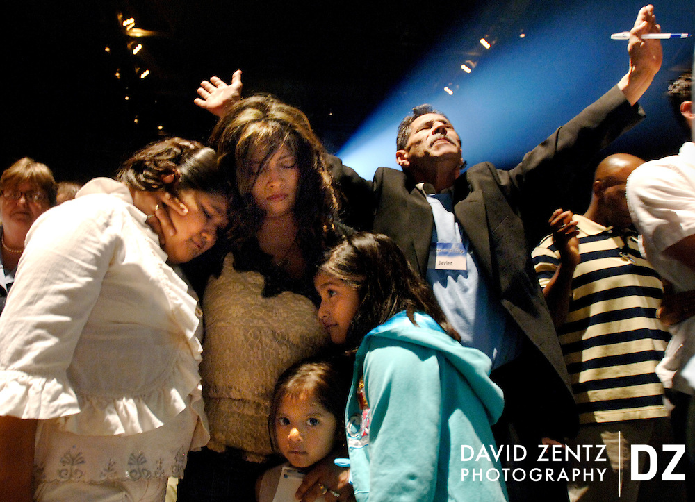 Araceli Montesdeoca of Peoria prays with her daughters, left to right Monica Valentin, Adriana Valentin and Michelle Valentin and friend Javier Trevino, right, at an Easter service in Peoria, Ill.