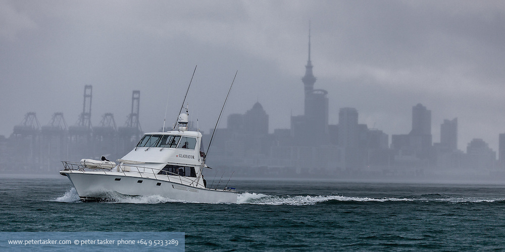 A fishing charter boat departs Auckland Harbour on a rainy winters day. Background silhouette of downtown Auckland visible through the rain.