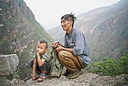 LIANGSHAN, CHINA - MAY 14: (CHINA OUT) <br /> <br />  Father and son from Atuler village rest at the cliff on their way to go home after school on May 14, 2016 in Liangshan Yi Autonomous Prefecture, Sichuan Province of China. 72 families lived in Atuler village on the 800-meter cliff at Meigu River Canyon in Liangshan Yi Autonomous Prefecture. 15 pupils, aged 6 to 15, accompanied by 3 adults regularly spent 2 hours climbing 17 vines ladders hung on the 800-meter-high cliff to go between school and home twice a month. Villagers used the same ladders to go to the nearest market once a week to sell peppers and walnuts and buy necessities.<br /> ©Exclusivepix Media