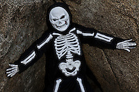 Boy dressed up as skeleton posing on rock