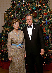 Dec 05, 2004; Washington, D.C., USA; President GEORGE W. BUSH and LAURA BUSH stand in front of the official White House Christmas Tree during the 2004 holiday season in the Blue Room of the White House. The White House celebate the holidays with, 'A Season Of Merriment and Melody,' and include items like 350 instrument ornaments that adorn the Blue Room tree.