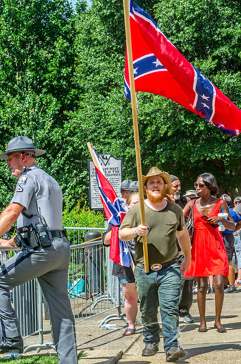 A man carries a Confederate flag outside the South Carolina State House, July 10, 2015, in Columbia, S.C. Thousands flocked to the South Carolina Statehouse to see the removal of the Confederate flag. The flag flew above the capitol dome from 1961-2000, then was moved to the grounds. The flag, which is now permanently removed, will be stored at the Confederate Relic Room and Military Museum. The House voted for its removal after the shooting of nine African-Americans at Emanuel African Methodist Episcopal Church in Charleston, June 17, 2015. Alleged shooter Dylann Roof, who published a manifesto on his website supporting white supremacist beliefs, was seen in numerous photographs holding the Confederate flag. (Photo by Carmen K. Sisson/Cloudybright)