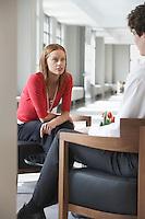 Businesswoman sitting talking to businessman