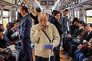 Blinder Mann mit einer Mundharmonika musiziert in der Metro in Seoul zwischen anderen Reisenden um sich etwas zusaetzliches Geld zu verdienen. ..Blind man with a mouthorgan is doing music for earning some more money in between passengers of the Seoul Metro.