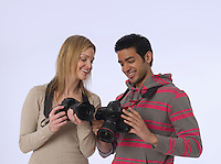 Young photographers with cameras studio shot