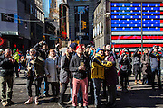 Groups of tourists look up to see their photos appear on the large digital screen in Times Square Midtown Manhattan, New York City, New York, United States.   Behind them is a large screen of the large American Flag on the side of the US Armed Forces Recruiting Station.  (photo by Andrew Aitchison / In pictures via Getty Images)