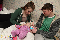 Teenage couple playing with baby