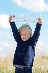 little boy holding up the word Peace at the beach