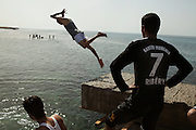 Libyan boys dive in to the sea at the beach of Zawiyah..Several rebel fighters of the Zawiyah Brigade give the compensation they had from the provisorial governement to the local council to support the construction of  tourist infrastructures and try to rebuild a local economy..Zawiyah was one of first cities to uprise against Qaddafi. The Zawiyah Brigade oppose strong resistance to the loyalists troops but after they loose the control of the city in March they had to flee toward the mountains of Jebel Nafusa and fight in the desert for months before to be able to reconqueer the city in the month of August during the offensive that lead the rebel brigades to take Zawiyah and after the Capital Tripoli.
