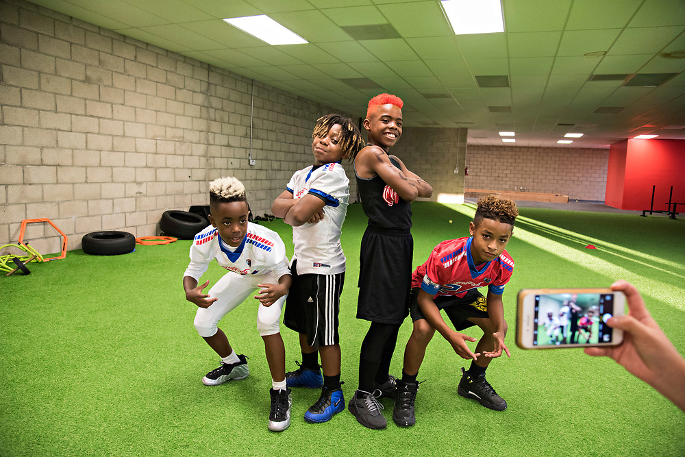 "Collectively, when they play they're knows as the Laced Facts Kids, but individually they are: Ca'ron Williams, Champ Brown, Maxwell ""Bunchie"" Young, and Therman ""Boogie"" Williams (left to right), and they're posing for pictures for their moms after training. They're all friends who met at the Laced Facts elite football training school. ""All of them are well know to college scouts,"" said Laced Facts owner and head coach Mike Evans, a former Louisville football player and product of South L.A. himself. Bunchie has already gotten a D-1 football scholarship offer from the Illinois Fighting Illini, and on track to be a top recruit in the Class of 2025."