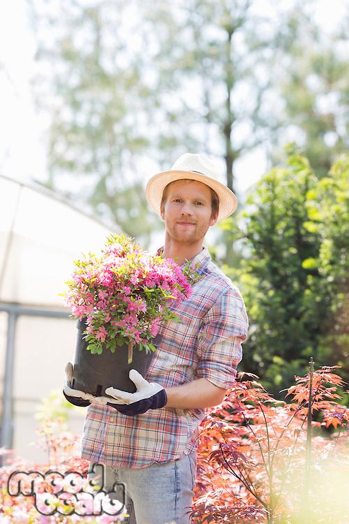 Portrait of gardener holding flower pot outside greenhouse