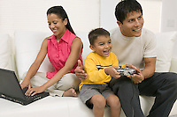 Father playing video game with son by mother using laptop on couch