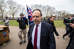 © Licensed to London News Pictures. 05/12/2017. London, UK. An anti-brexit protester chases and shouts at Nigel Dodds MP, Deputy Leader of the DUP, after he delivered a statement to the media in Victoria Gardens. Photo credit: Rob Pinney/LNP