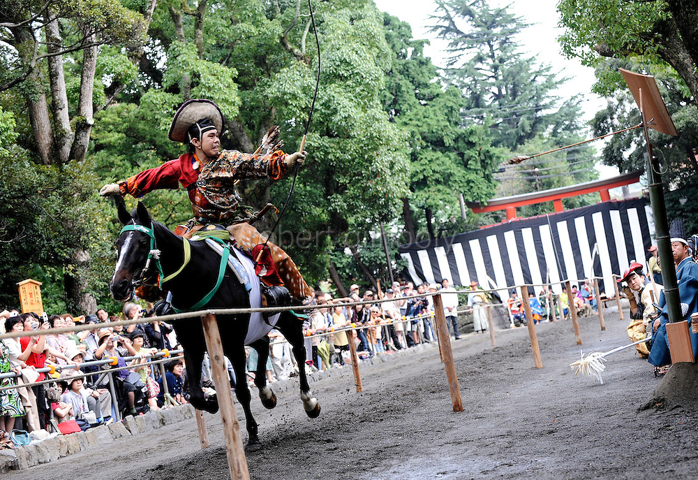 A horseback archer dressed in a traditional hunting garb aims an arrow at a target as his horse gallops along a 255-meter course at full pace during the Yabusame Shinji, a Japanese ritual, at Tsurugaoka Hachimangu shrine in Kamakura, near Tokyo. The ritual, which dates back to the 12th century and is aimed at appeasing the numerous gods that guard Japan, was initiated by Kamakura shogun Minamoto no Yoritomo  in an attempt to improve his samurai warrior's appalling archery skills..