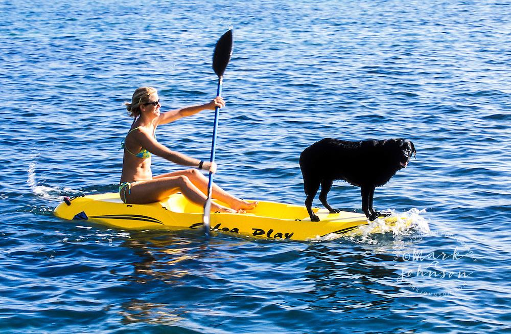 Woman & dog paddling on kayak, Oahu, Hawaii