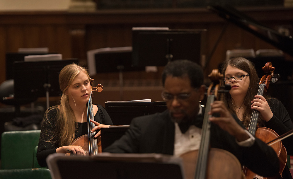 Sophie Kivlehan, (left) a freshman at Dickinson College,  warms up with other musicians in The Dickinson College Orchestra at the First Evangelical Lutheran Church in Carlisle. Kivlehan is one of 21 young plaintiffs suing the federal government on climate change. Seated in front of Kivlehan is her cello professor and cell principal Michael Cameron.