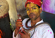 A priest of the Krishna Temple of Shriji, during Lathmar Holi, plays with a snake charmer freind's snake and blesses it with pink powder for Holi. The spectacle is a riot of colour amidst frenzied celebrations.