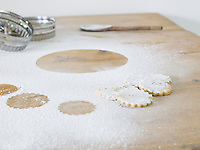 Pastry cutters cookies and flour scattered on table close up