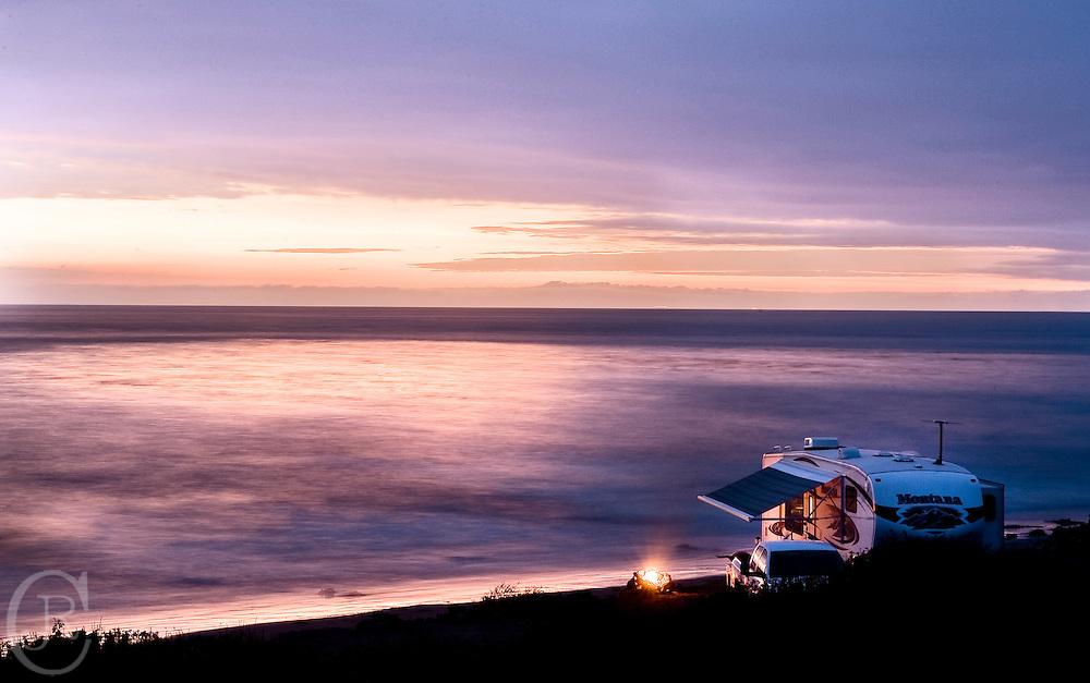 Vacationers enjoy a beautiful sunset on Emma Wood Beach Ventura California.
