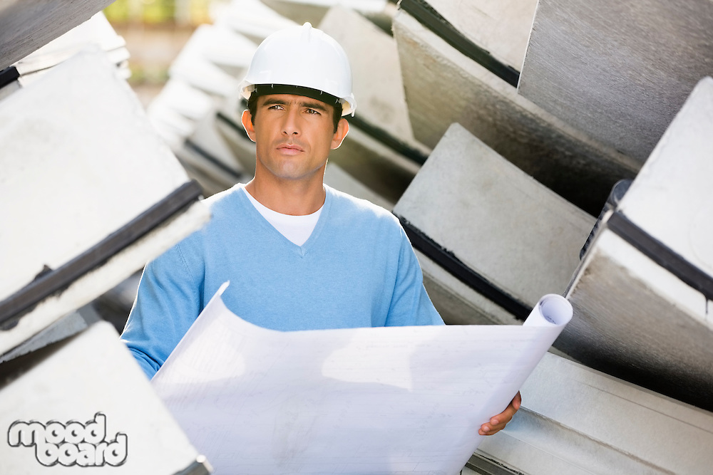 Male architect with blueprint working at construction site