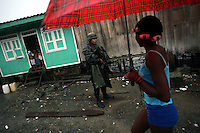A police officer keeps watch in Lleras, a poor barrio in Buenaventura, on the Pacific Coast of Colombia, on Tuesday, May 15, 2007. Buenaventura is in the midst of a spree of violence over control of drug shipments from the poor barrios in the city. Many of the neighborhoods have a strong presence of FARC militias that control most of the drug trade in the city. (Photo/Scott Dalton)