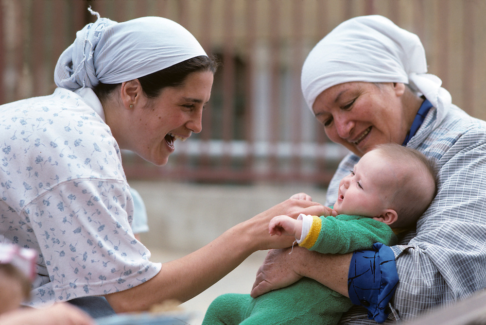 Israel, Orthodox Jewish women play with child in West Bank settlement.