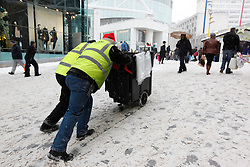 ©London News Pictures. 01/12/2010. Staff from the Bullring carry out the task of pushing the salt bin upto the main entrance of the shopping centre. On the busiest shopping day of the year people brave the snow and head out to the centre of Birmingham today (Sat).  Photo credit should read Alison Baskerville/London News Pictures