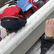 "Winter Olympics, Vancouver, 2010.The Slovakian team are helped by medical staff after finishing the  race on their side after crashing during the Bobsleigh, Four-Man heat two at The Whistler Sliding Centre, Whistler, during the Vancouver Winter Olympics. 26th February 2010. Photo Tim Clayton..'BOB'..Images from the Four-man Bobsleigh Competition. Winter Olympics, Vancouver 2010..History was made at the Whistler Sliding Centre when the USA four-man bobsleigh team, led by Steven Holcomb took the Gold. The first time since 1948, a gap of 62 years, since the USA have won an Olympic Bobsleigh gold and they did it with their sleigh named ""Night Train""...The four days of practice and competition show the tension, nervousness and preparation as the teams of hardened men cope with the challenge of traveling at average speeds of over 150 km an hour. Indeed, five teams had already pulled out of the event before the opening heats because of track complexity, speed and fear, and on the final day, another four teams did not start after six crashes in the first two heats...Teams warm up behind the start complex, warming muscles in the cold in preparation for the explosive start. Many teams prepare in silence, mentally preparing themselves as they wait at the top of the run, in the bobsleigh sheds and the loading areas for their turn. When it's time to slide each team performs it's own starting ritual, followed by the much practiced start out of the blocks for just over four seconds, the teams are then in the hands of the accomplished drivers as they hurtle down the track for just over fifty seconds...Spectators clamber for the best position on track to see the sleighs for a split second, many unsuccessfully try to capture the moments on camera, The rumble of the sleigh is heard then the crowds gasp as it hurtles past in a blur...The American foursome of  Steven Holcomb, Justin Olsen, Steve Mesler and Curtis Tomasevicz finished with a pooled four-heat time of 3min 24.46sec. The Ger"