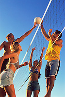 Volleyball players jumping to hit ball, view from below